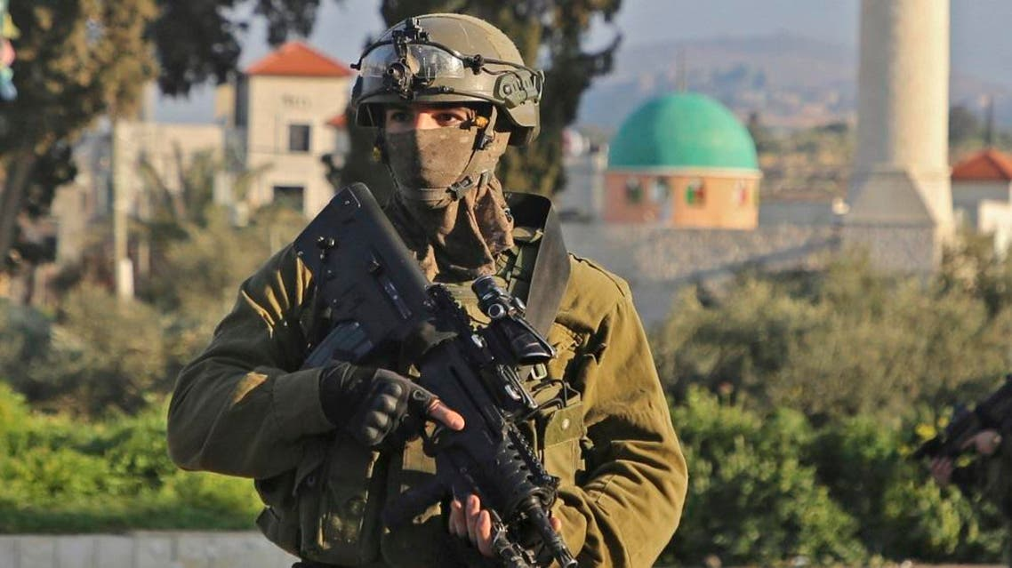An Israeli soldier stands guard in a street in the northern West Bank village of Salem, east of Nablus, on March 18, 2019. (AFP)