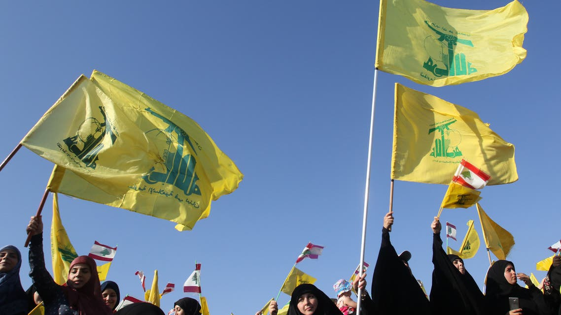 Supporters of the Lebanese Shiite movement Hezbollah fly the group's flag during a speech by the leader to mark the 11th anniversary of the end of the 2006 war with Israel, in the village of Khiam in southern Lebanon on August 13, 2017.