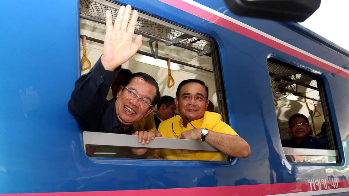 Cambodia's PM Hun Sen waves beside Thailand's PM Prayut Chan-O-Cha as they ride a train during a ceremony to connect the railway line between Cambodia and Thailand on April 22, 2019. (AFP)