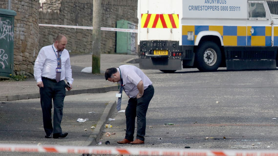 (FILES) In this file photo taken on April 19, 2019 Police detectives inspect the scene where a journalist was fatally shot amid rioting overnight in the Creggan area of Derry (Londonderry) in Northern Ireland on April 19, 2019. The killing of journalist Lyra McKee in Derry on April 18, 2019 marked the latest upsurge of violence in Northern Ireland -- where fears grow that a fragile and hard-won peace is increasingly at risk.