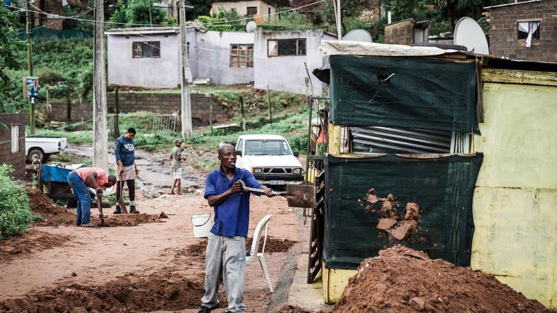 People begin to clear debris at an informal settlement of BottleBrush, south of Durban, after torrential rains and flash floods caused huge damages to their homes on April 23, 2019. The death toll from floods and mudslides that crushed homes in the South African port of Durban on April 23 has risen to 33, with reports of children missing and scores of people displaced, authorities said. RAJESH JANTILAL / AFP