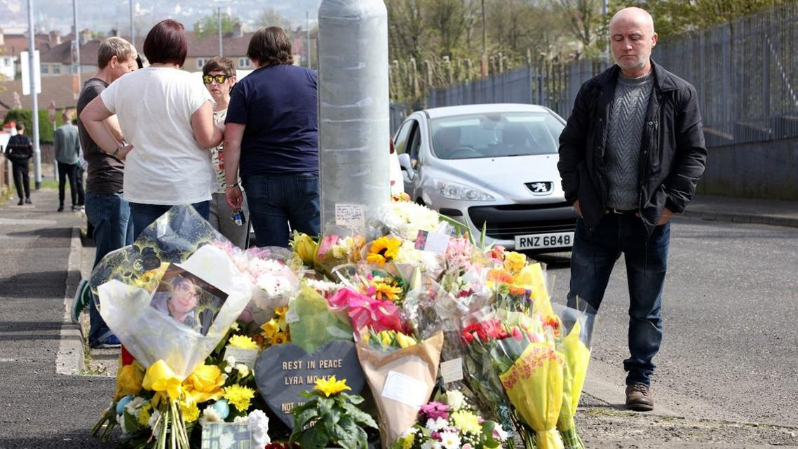 People gather around the floral tributes placed at the scene in the Creggan area of Derry (Londonderry) in Northern Ireland on April 20, 2019, where journalist Lyra McKee was fatally shot amid rioting on April 18. (AFP)
