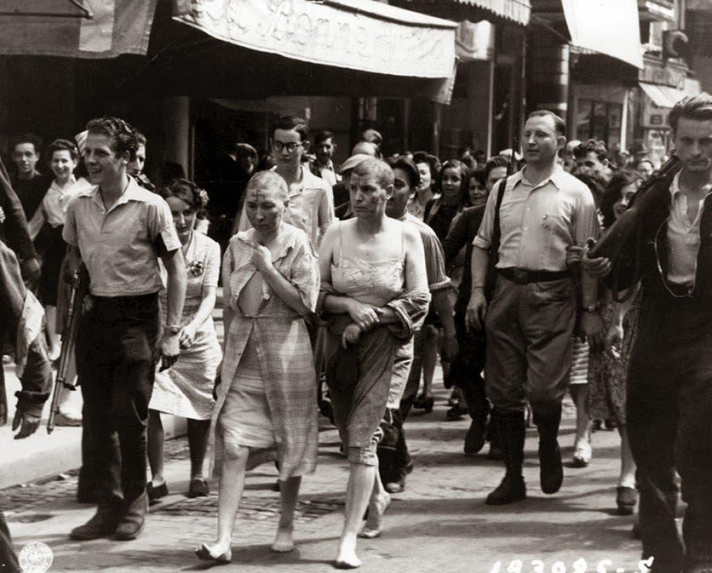 صورة لنساء فرنسيات متهمات بالخيانة خلال عرضهن بالشوارع عقب حلق رؤوسهن و رسم علامة الصليب المعقوف على جبهاتهن