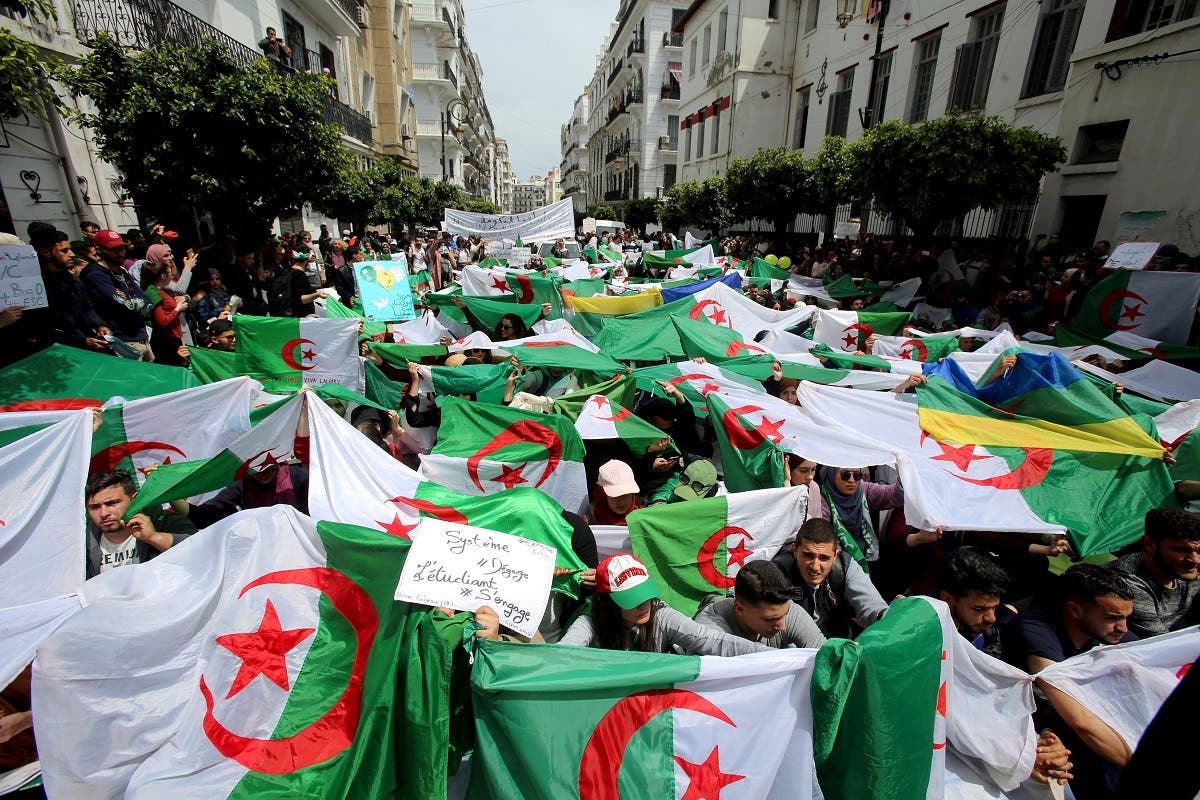 Demonstrators hold flags and banners during anti-government protests in Algiers. (Reuters)