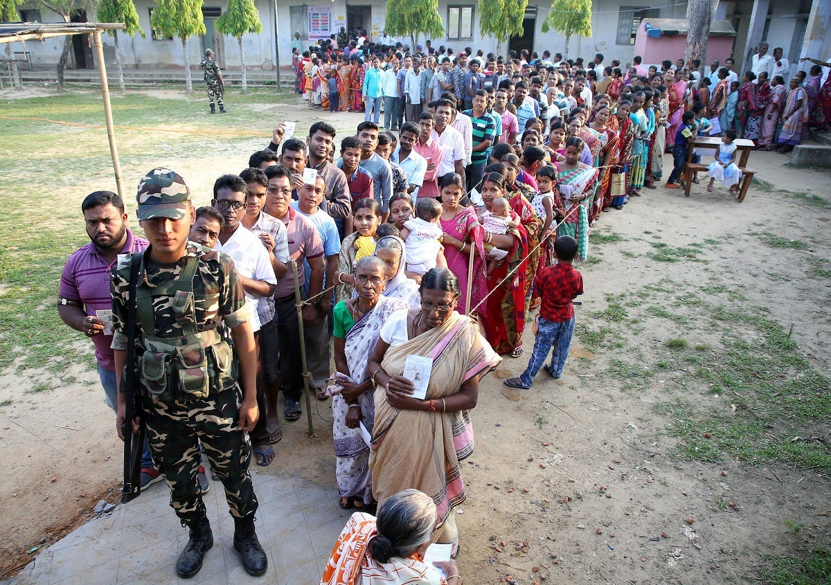 A security trooper stands guard as people wait in queues to cast their votes outside a polling station during the third phase of general election in Khowai district in the northeastern state of Tripura, India, on April 23, 2019. (Reuters)