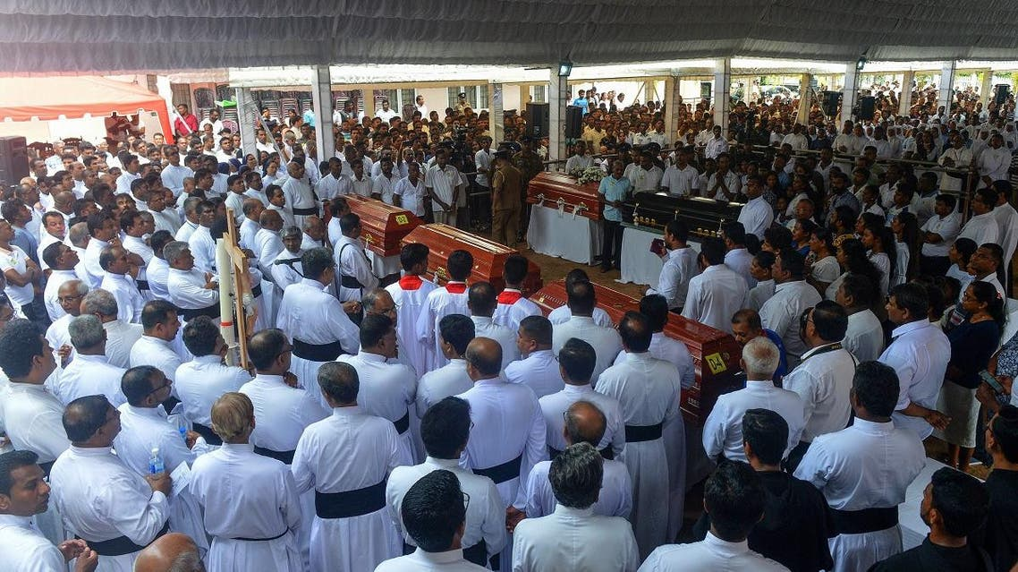 Sri Lankan priests and relatives bless the coffins of bomb blast victims after a funeral service at St. Sebastian's Church in Negombo on April 23, 2019. (AFP)