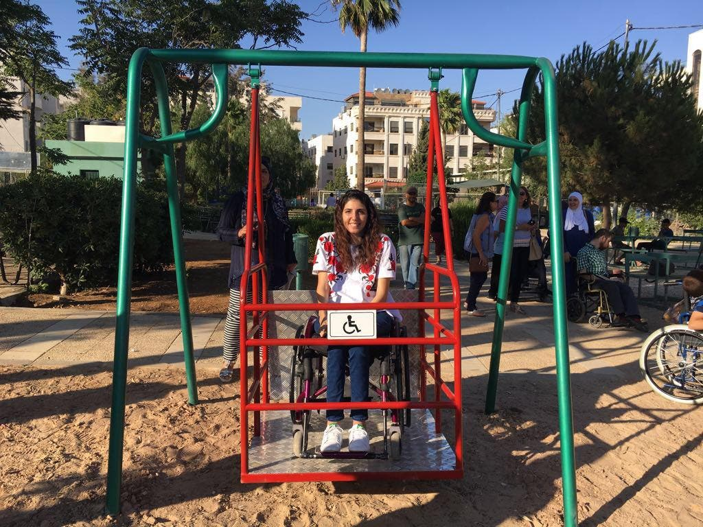 Aya sits in one of her newly installed swings for PWDs in a public park in Jordan.