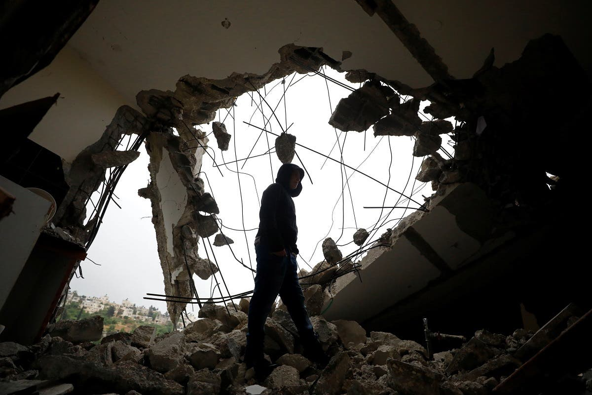 A man walks inside the house of Palestinian assailant Saleh Al-Barghouti after it was partially demolished by Israeli forces in the village of Kobar near Ramallah, in the Israeli-occupied West Bank, on April 17, 2019. (Reuters)