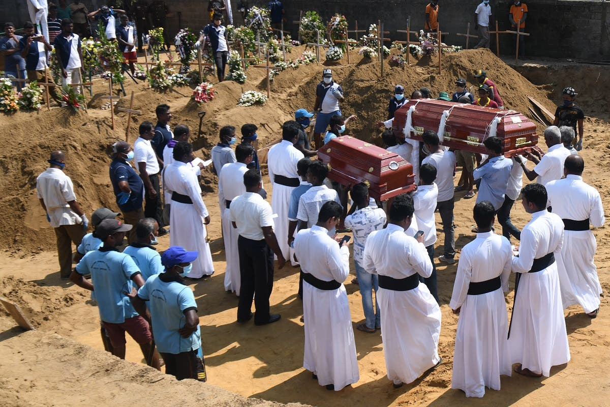 Relatives carry coffins of bomb blast victims for a burial ceremony at a cemetery in Negombo on April 24, 2019. (AFP)