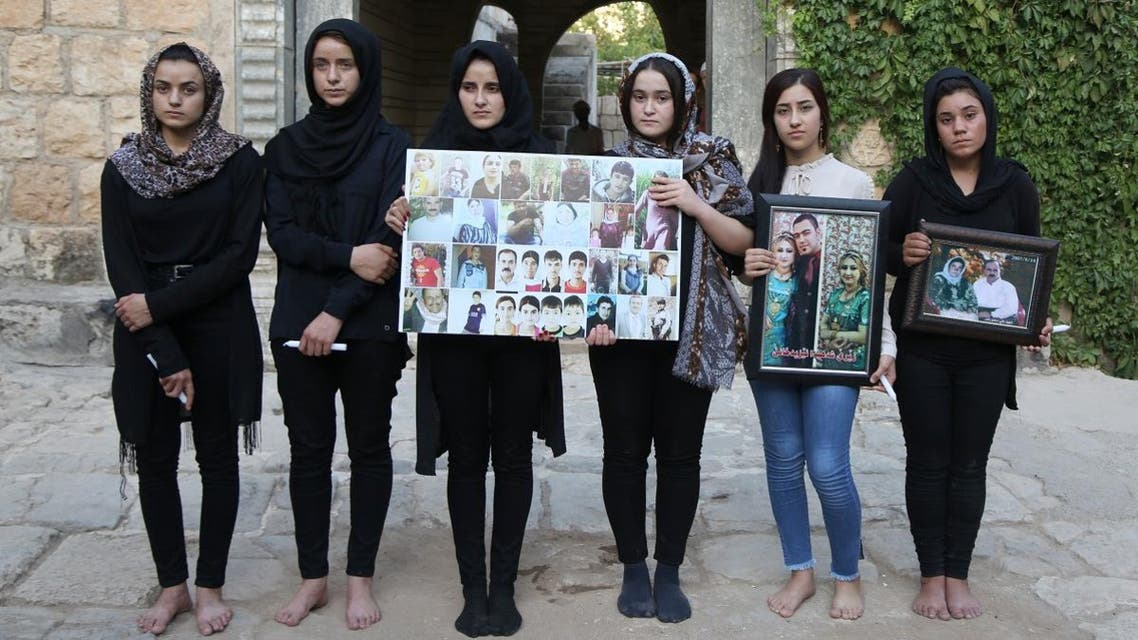 Yazidi woman Ashwaq Haji (1st-L) allegedly used by ISIS as a sex slave, poses for a photograph in tribute to victims from her village of Kocho near Sinjar. (File photo: AFP)