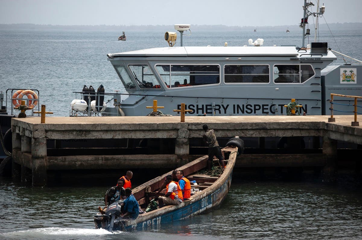 Chinese fishermen in a wooden carved boat are seen at the port in Freetown's Murray Town suburb on April 8, 2019 with the only Joint Maritime Committee (JMC) offshore patrol boat, donated by the World Bank, in the background. (AFP)
