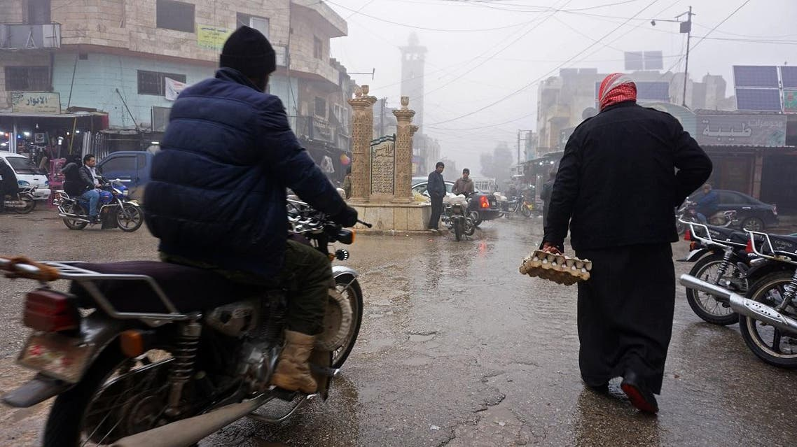 A Syrian man rides his motorcycle past a pedestrian in the village of Kafranbel in the northwestern province of Idlib. (AFP)