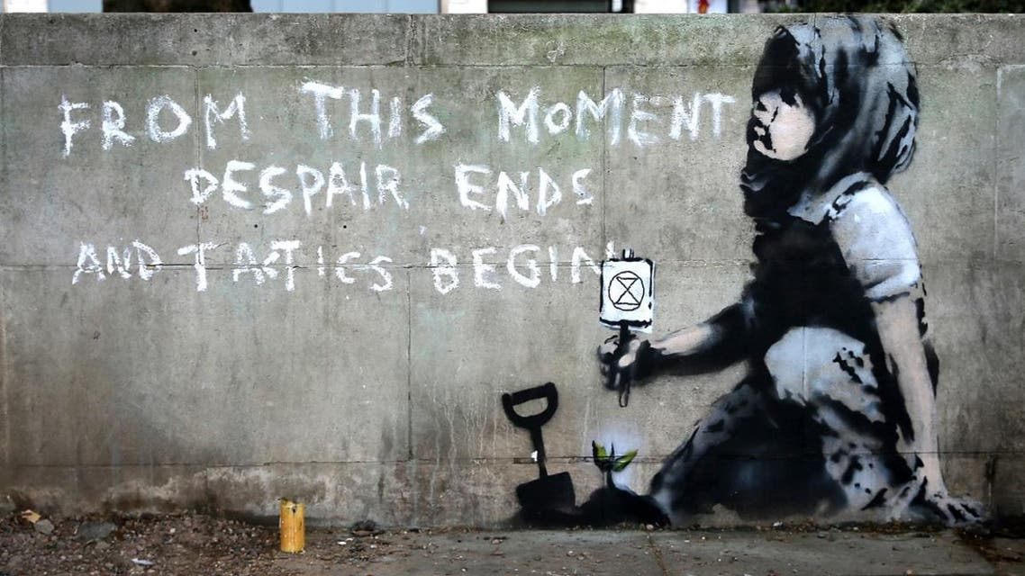 Graffiti artwork, suspected to have been created by the British street artist Banksy, is pictured opposite the environmental protest group Extinction Rebellion's camp at Marble Arch in London. (AFP)
