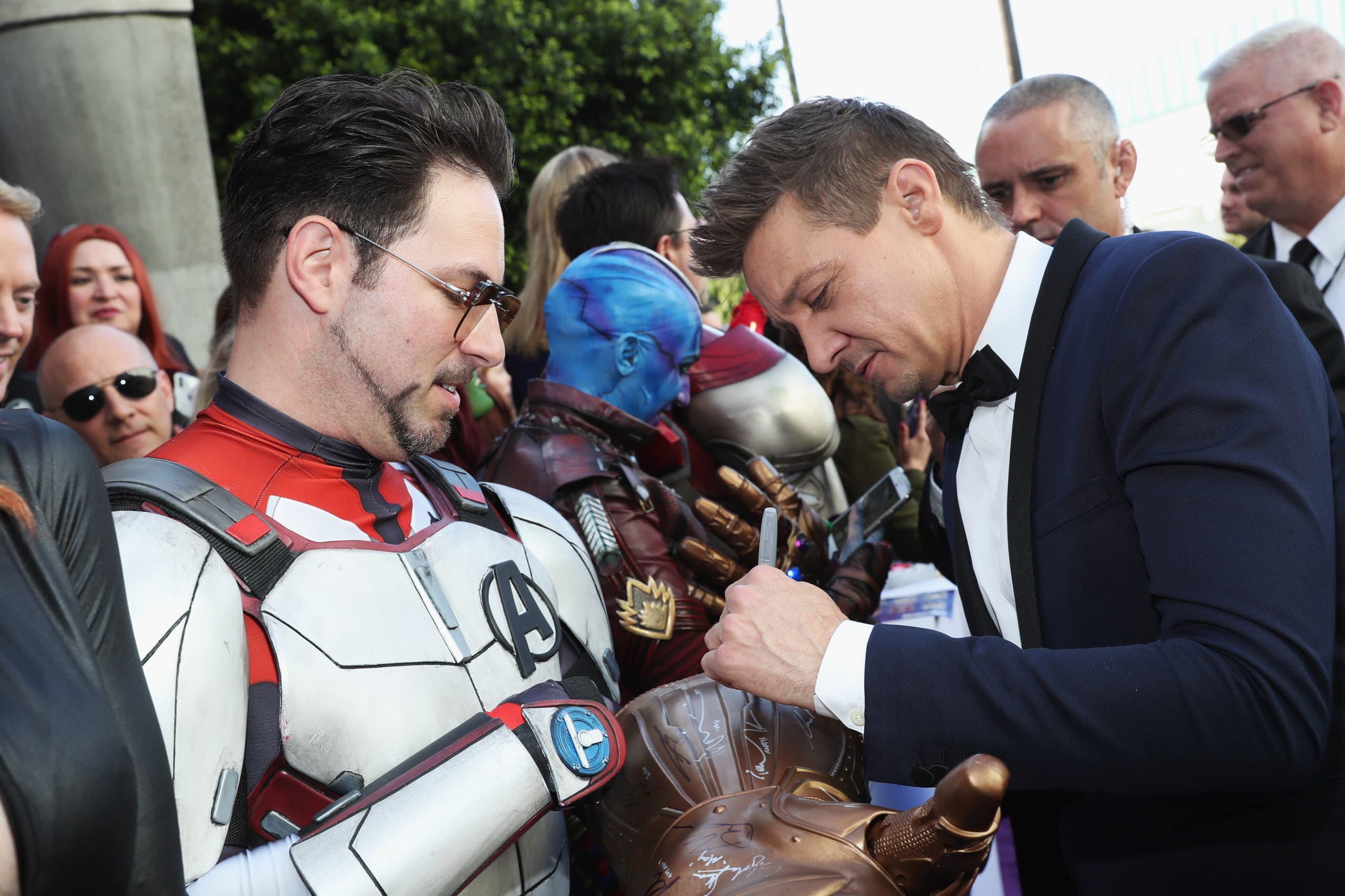 Jeremy Renner signs a fan's costume at the Avengers: Endgame premiere. (AFP)