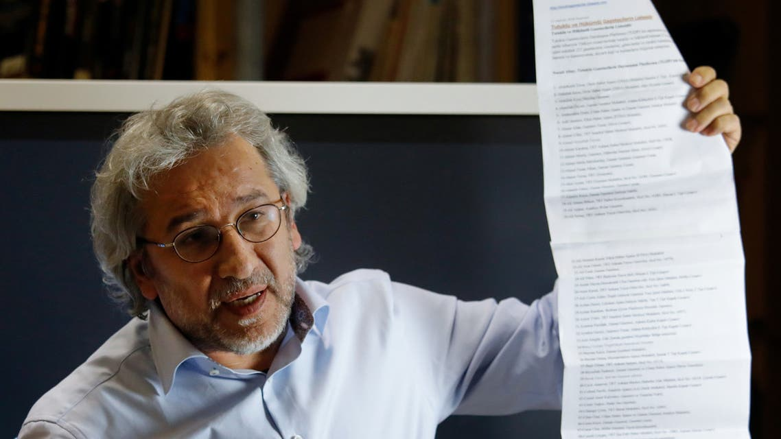 Can Dundar, Turkish journalist and former chief editor of the Turkish daily newspaper Cumhuriyet, holds up a list of journalists in prison in Turkey at a press conference in Berlin on September 28, 2018. Turkish President Recep Tayyip Erdogan confirmed in Berlin that his country is seeking the extradition of Turkish journalist Can Dundar, currently in exile in Germany. Dundar is evading a jail sentence for his Cumhuriyet newspaper's reporting on alleged secret Turkish arms deliveries to Islamist rebels in Syria.