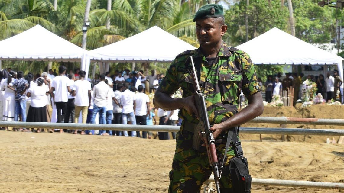 A Sri Lankan soldier stands guard during a burial ceremony for bomb blast victims in a cemetery in Negombo, after a series of bomb attacks targeting churches and luxury hotels in Sri Lanka. (AFP)