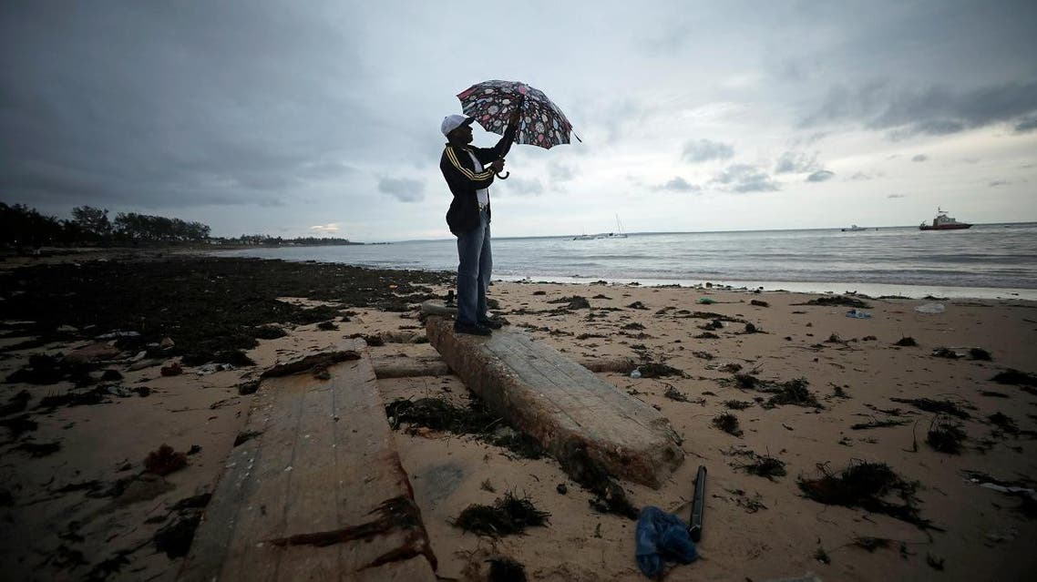 A man holds an umbrella beneath storm clouds over Wimbe beach in Pemba. (Reuters)