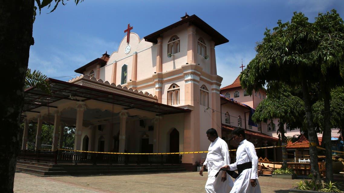 Sri Lankan Roman Catholic priests walk past damaged St. Sebastian's Church in Katuwapitiya village in Negombo, north of Colombo, Sri Lanka (AP)