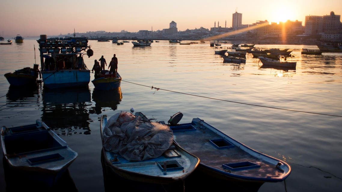 Palestinian fishermen arrive on their boats to the Gaza seaport - AP