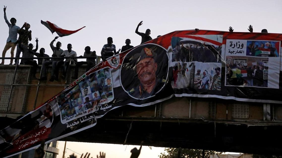 Protesters tear down a banner with a picture of Sudan's head of transitional council, Lieutenant General Abdel Fattah Al-Burhan Abdelrahman and pictures showing the Sudanese soldiers and protesters together, in Khartoum. (Reuters)