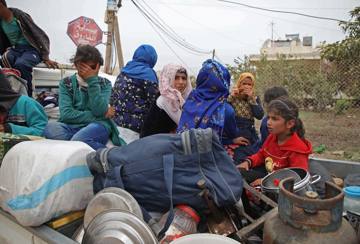 A Syrian family, riding in the back of a truck loaded with belongings, flee from reported regime shelling on Hama and Idlib provinces on May 1, 2019. (AFP)