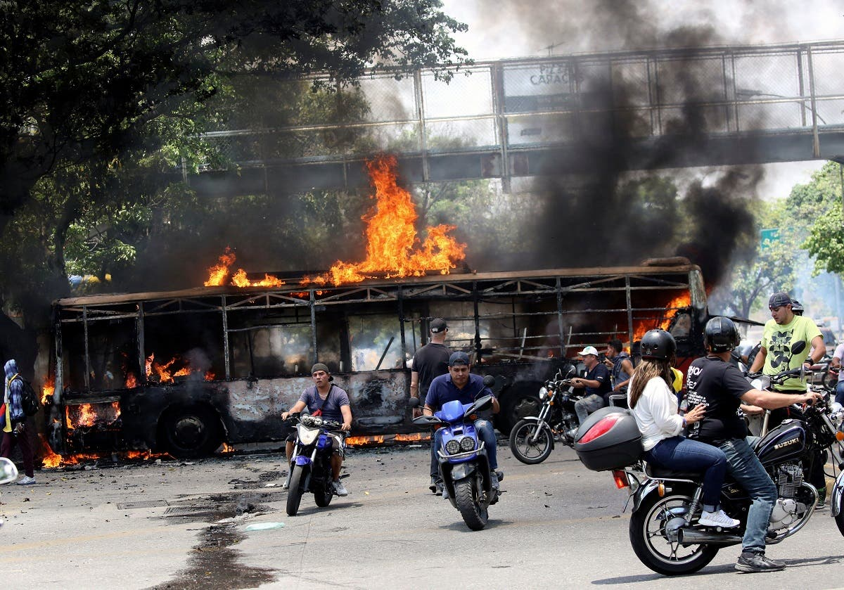 People drive their motorcycles near a burnt bus during anti-government protests, in Caracas. (Reuters)