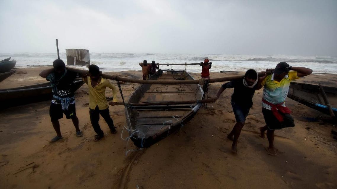 Indian men carry a fishing boat up a beach away from heavy waves in Gopalpur in eastern Odisha state. (File photo: AFP)