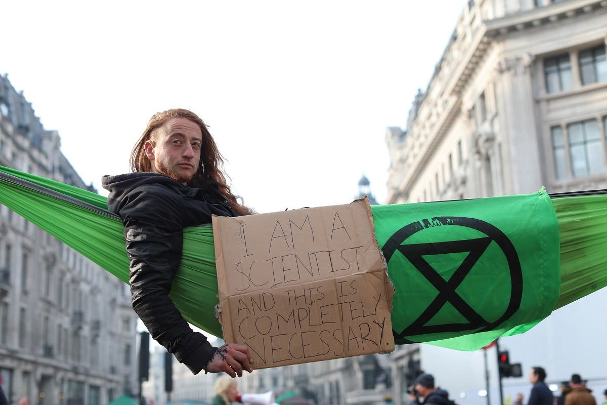 A climate change activist in a hammock occupying Oxford Circus in the busy shopping district of central London on April 18, 2019 on the fourth day of an environmental protest by the Extinction Rebellion group.  (AFP)