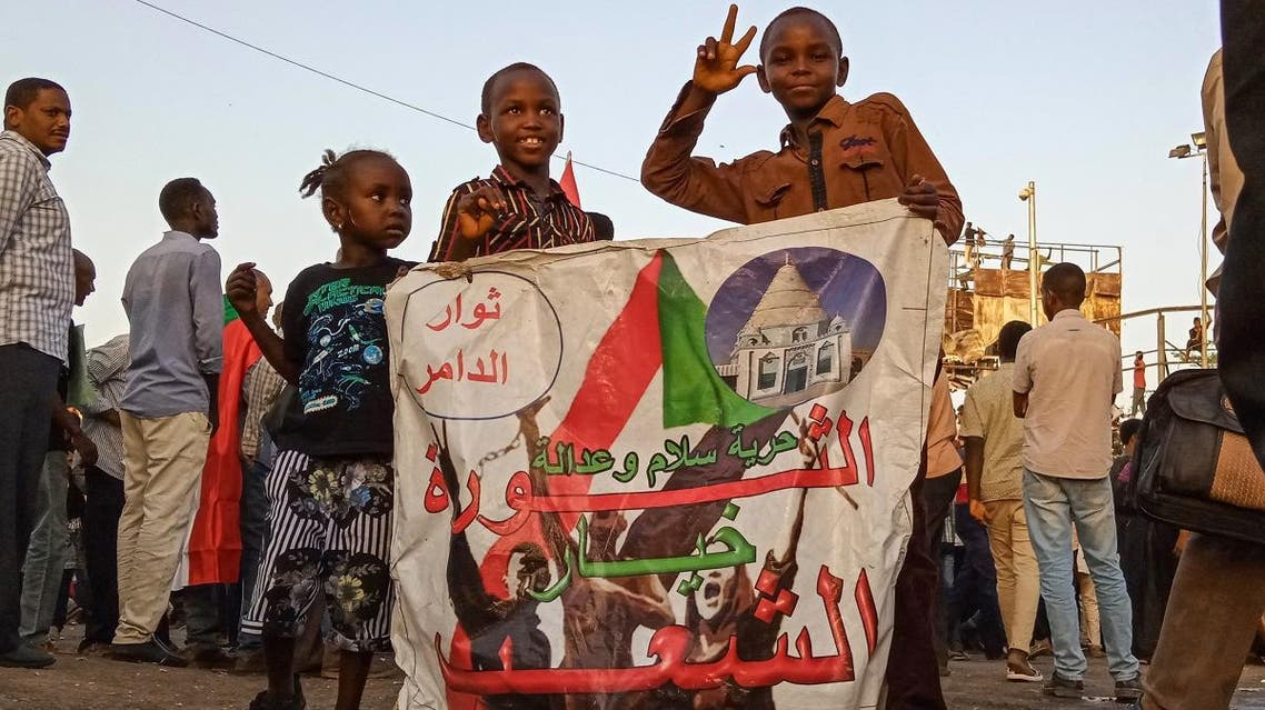 "Sudanese children hold a banner reading in Arabic ""Revolution is the choice of the people"" during a sit-in outside the army headquarters in Khartoum on May 2, 2019. (AFP)"