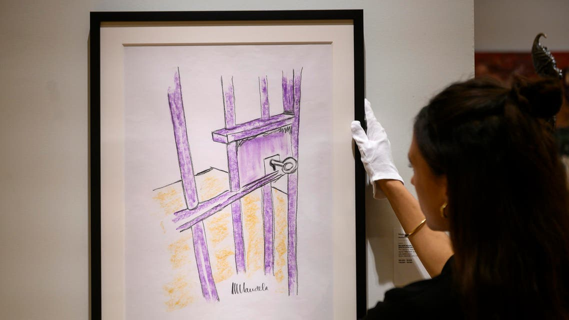 "A worker holds a sketch by Nelson Mandela -- ""The Cell Door, Robben Island"" -- on April 26, 2019 in New York City. AFP"