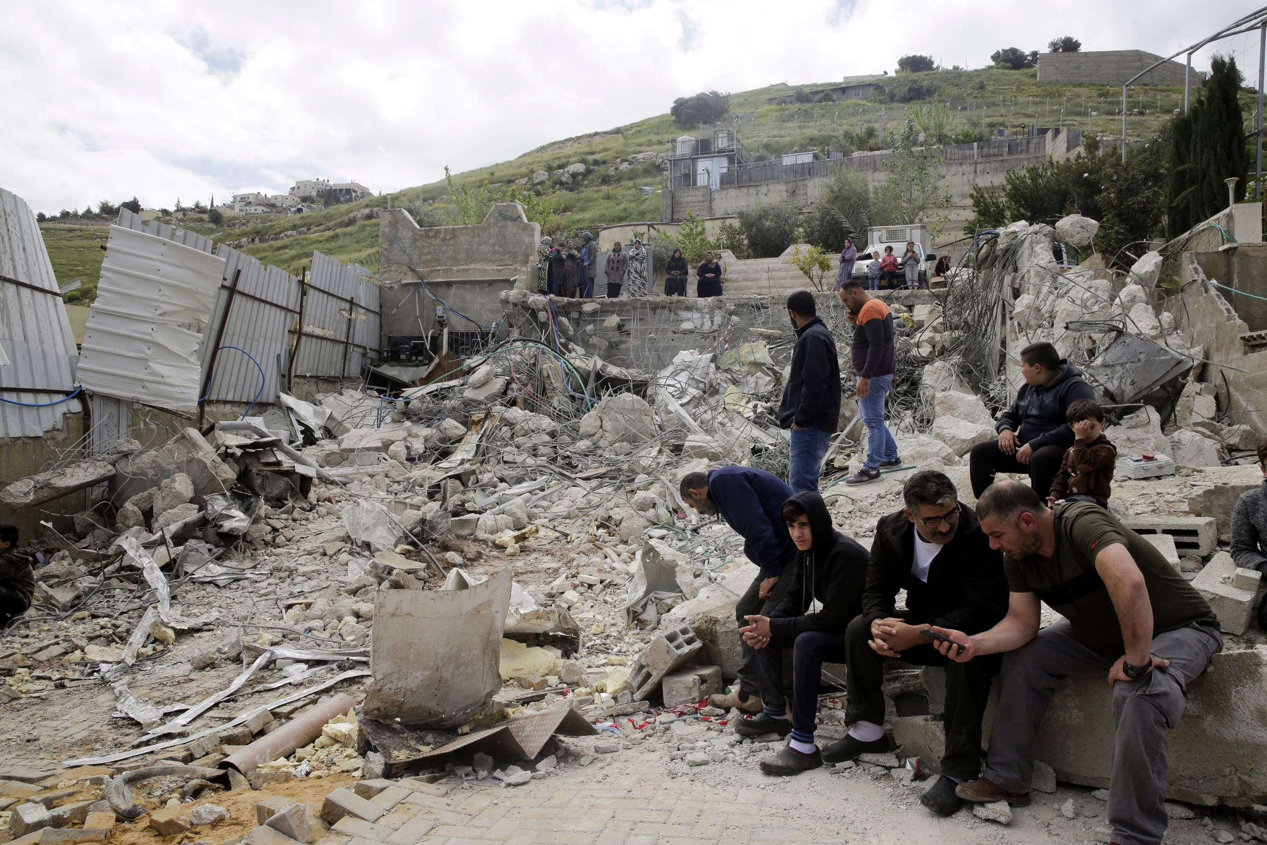 Palestinians sit by a family house destroyed by Israeli authorities in east Jerusalem's neighborhood of Silwan. (File photo: AP)