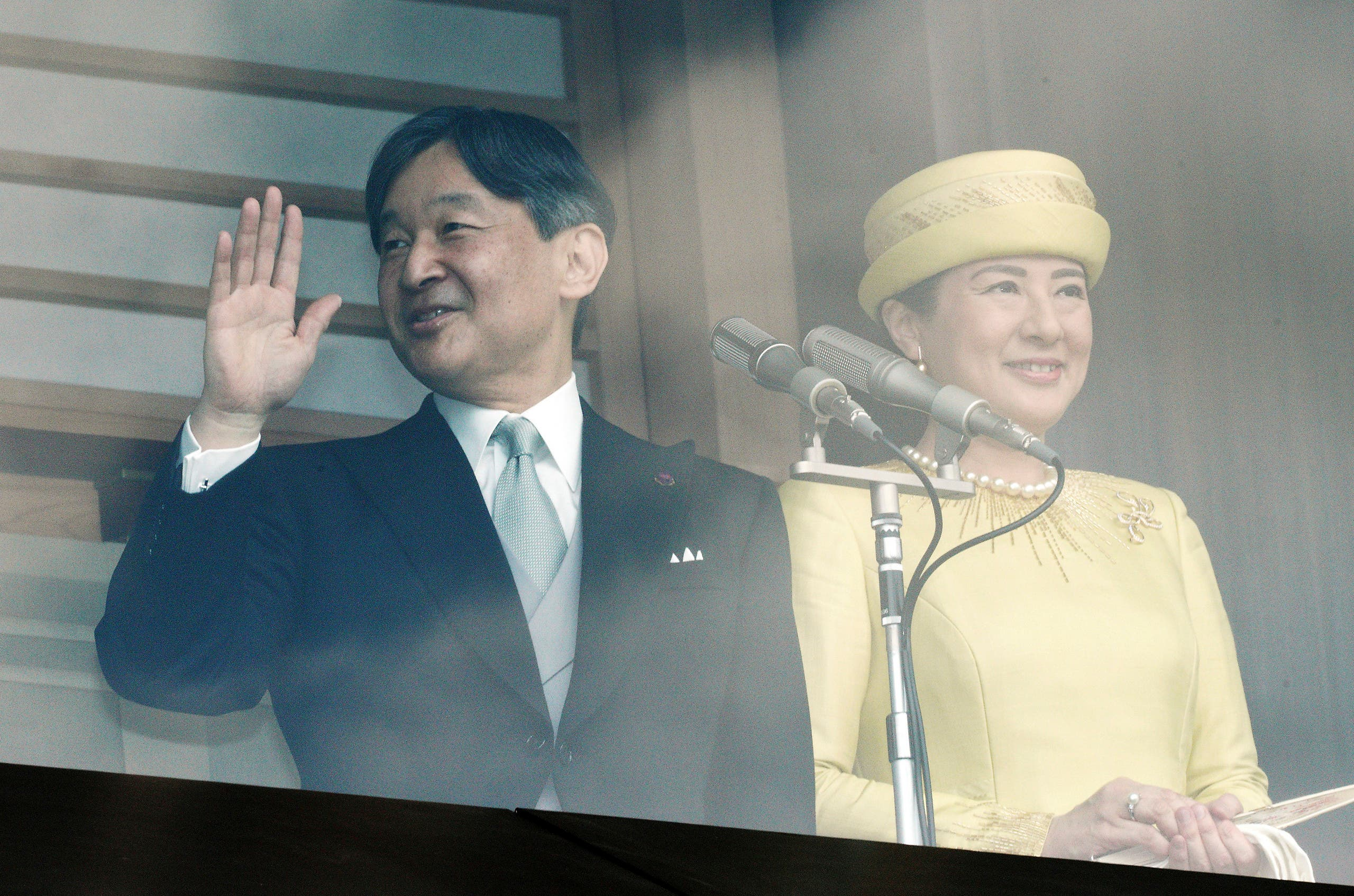 Japan's new Emperor Naruhito, left, waves with Empress Masako, right, to well-wishers from the balcony during his first public appearance with his imperial families at Imperial Palace Saturday (AP)