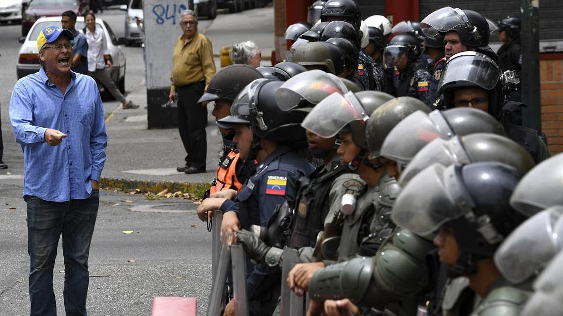 A man speaks to riot police during an opposition demo near La Carlota Air Base in Caracas on May 4, 2019. (AFP)