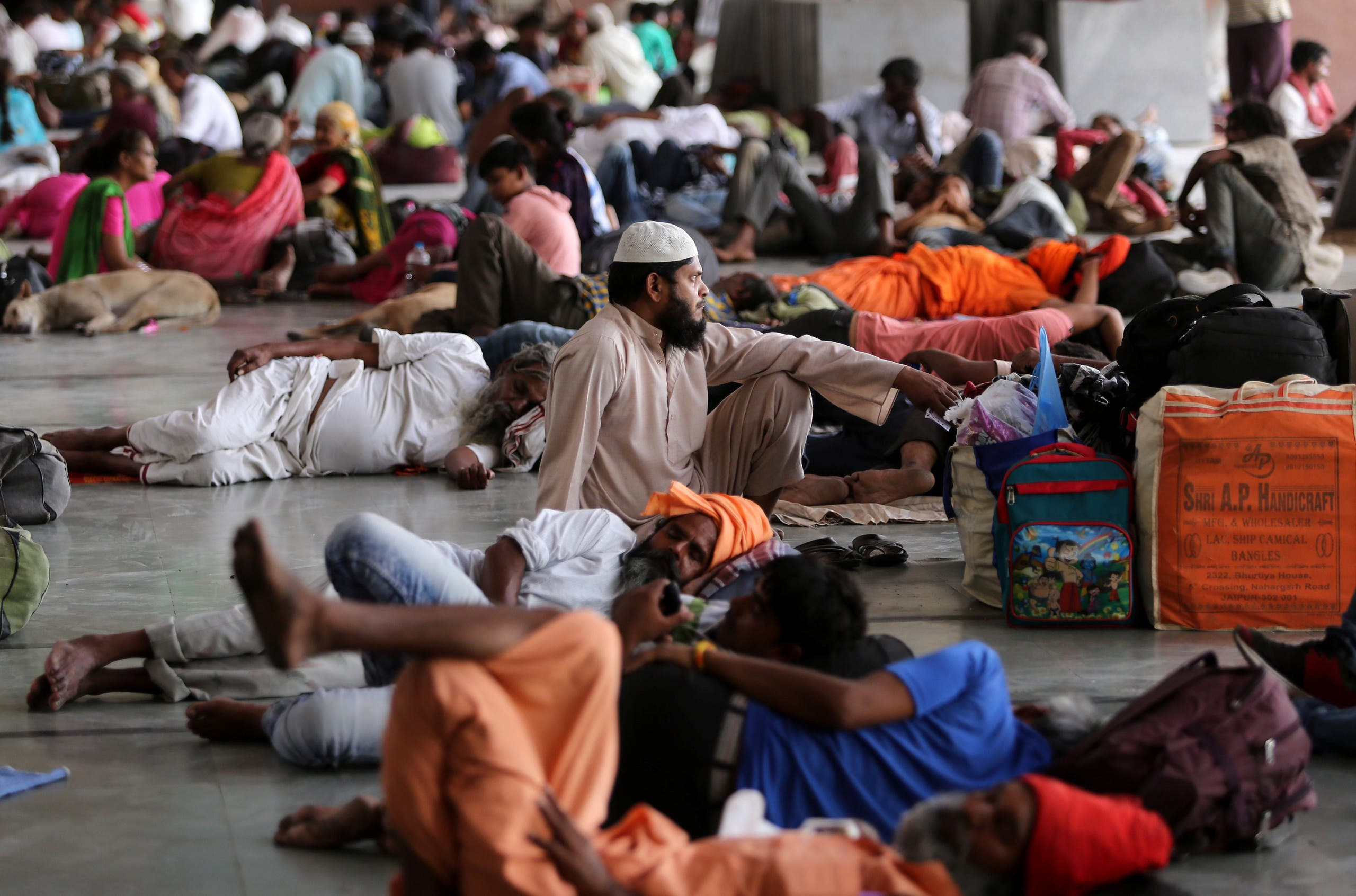 Stranded passengers wait for train services to resume at a railway station after their trains were cancelled following Cyclone Fani, in Ahmedabad, india  (Reuters)