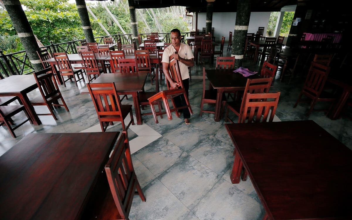 A man arranges chairs at an empty restaurant of the Warahena Beach hotel in Bentota. (Reuters)