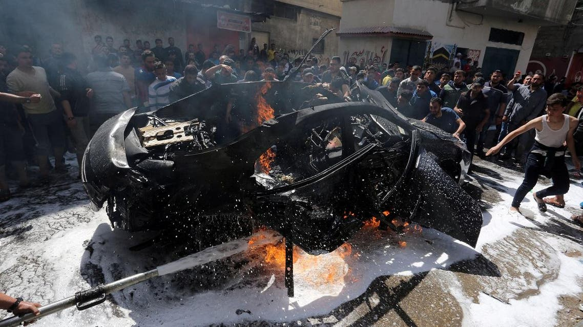 Palestinians try to extinguish a fire in the car of a Hamas commander who was killed in an Israeli air strike, in Gaza City May 5, 2019. (Reuters)