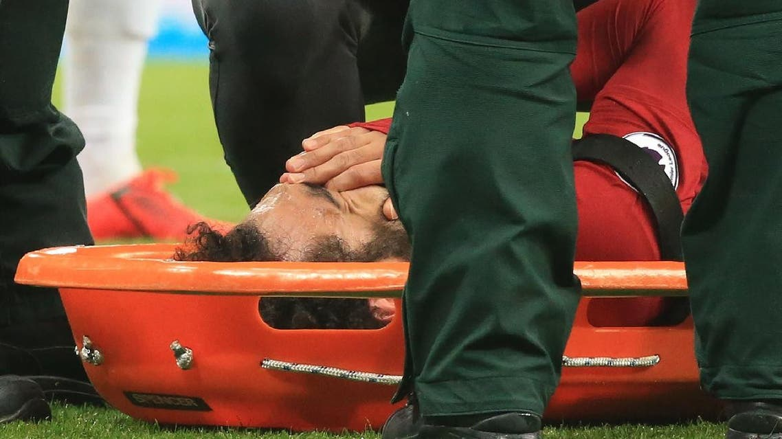 Salah reacts as he is placed on a stretcher after injuring himself. (AFP)