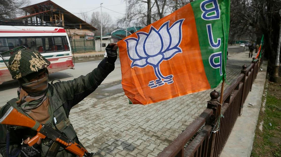 An Indian paramilitary soldier holds a flag of India's ruling Bharatiya Janata Party (BJP) as he stands guard during a meeting of the party ahead of the upcoming elections in Srinagar, Indian controlled Kashmir, Thursday, March 14, 2019. India's national election will be held in seven phases in April and May. (AP Photo/Mukhtar Khan)