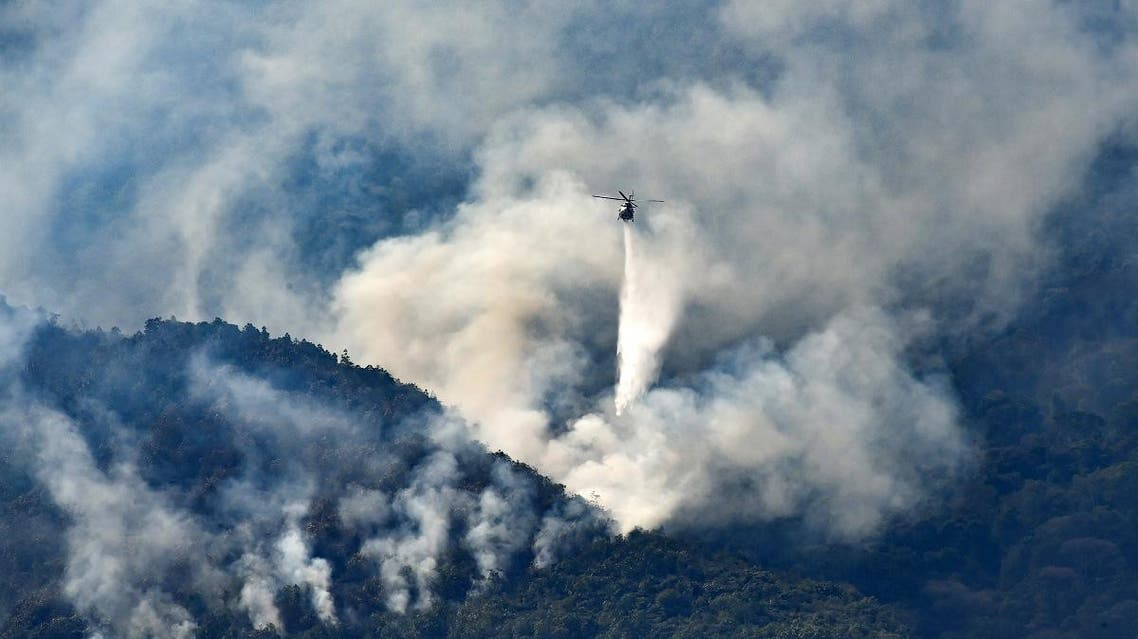 A government helicopter sprays dust during a wildfire at El Avila hill in Caracas, on April 2, 2019. El Avila hill is one of the sources where the population collects water, as it lacks due to power outages. YURI CORTEZ / AFP