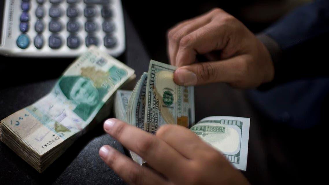 A Pakistani money changer counts US dollar bills in Islamabad, Pakistan, Friday, Nov. 30, 2018. (AP)
