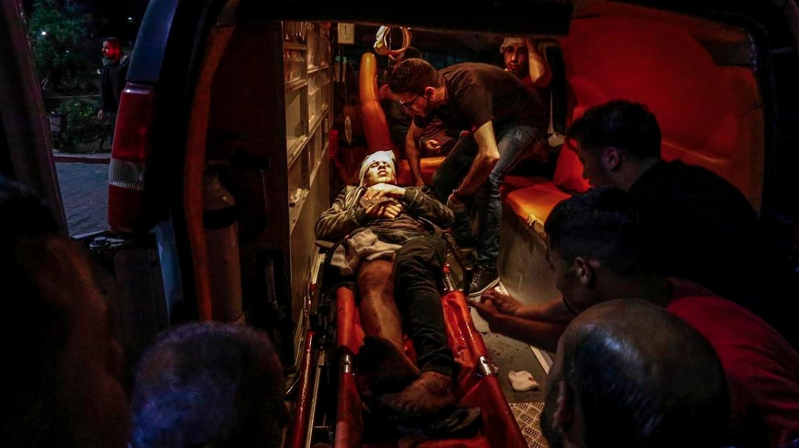 Paramedics carry the body of a wounded Palestinian at a hospital in Beit Lahia, northern Gaza strip on May 5, 2019. (AFP)