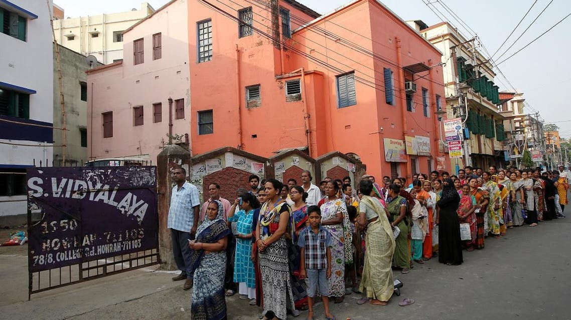 People stand in a queue to cast their vote outside a polling station during the fifth phase of general election in Howrah. (Reuters)