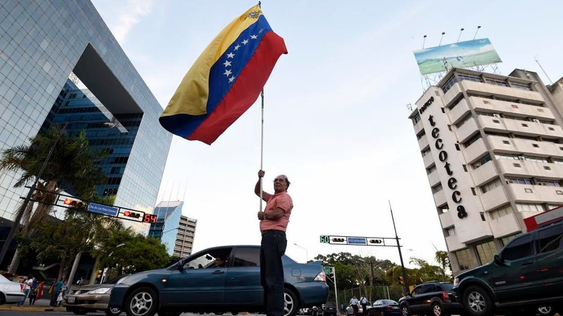 An anti-government demonstrator waves a Venezuelan national flag in the middle of the street in front of the Parque Cristal building. afp