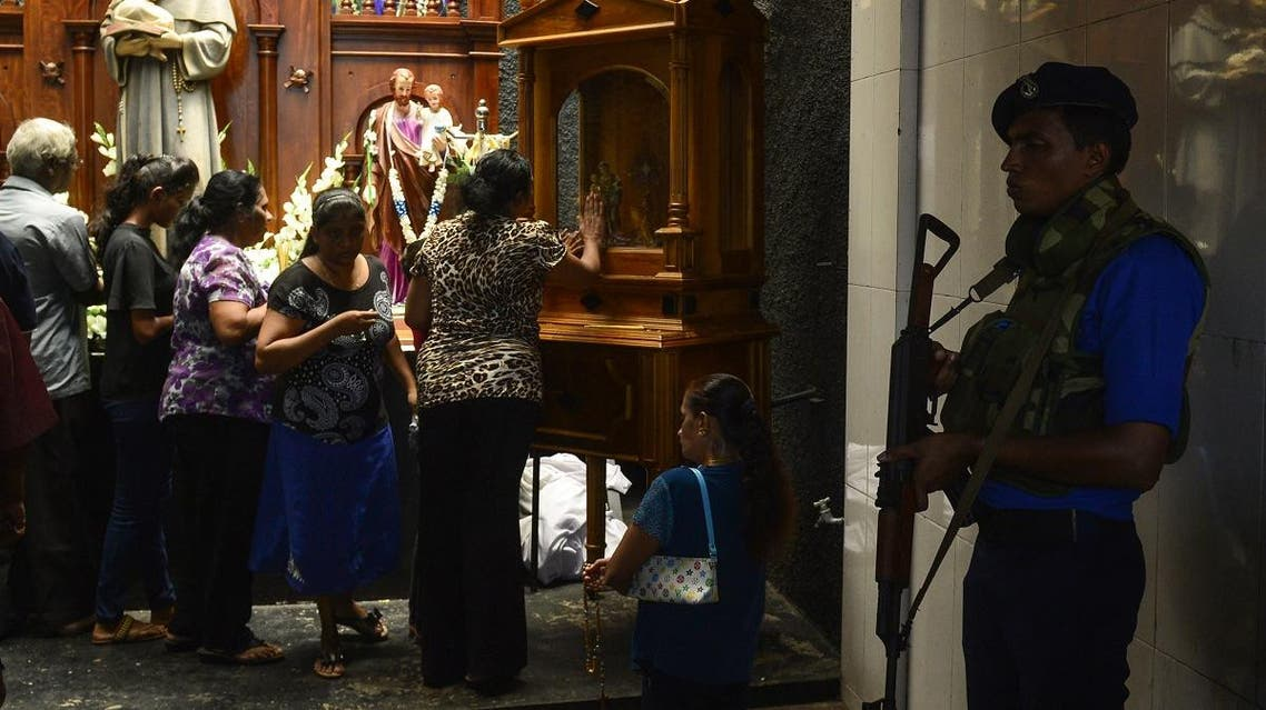 A Sri Lankan Navy personnel stands guard as Catholic devotees pray at St. Anthony's church on May 7, 2019. (AFP)