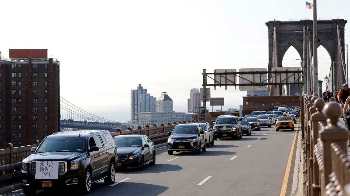 Uber and Lyft drivers, with signs on their vehicles supporting better wages, cross the Brooklyn Bridge in a caravan of about 25 vehicles, on May 8, 2019 in New York. (AP)