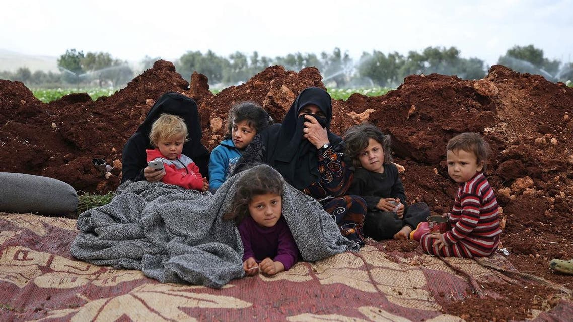 Displaced Syrians gather in a field near a camp for displaced people in the village of Atme, in the northern Idlib province on May 8, 2019. (AFP)