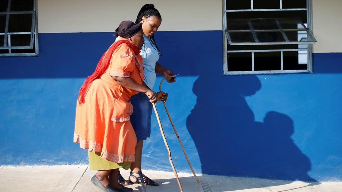 An Electoral Commission of South Africa (IEC) offical assits a blind voter to cast her ballot at a polling station. (Reuters)