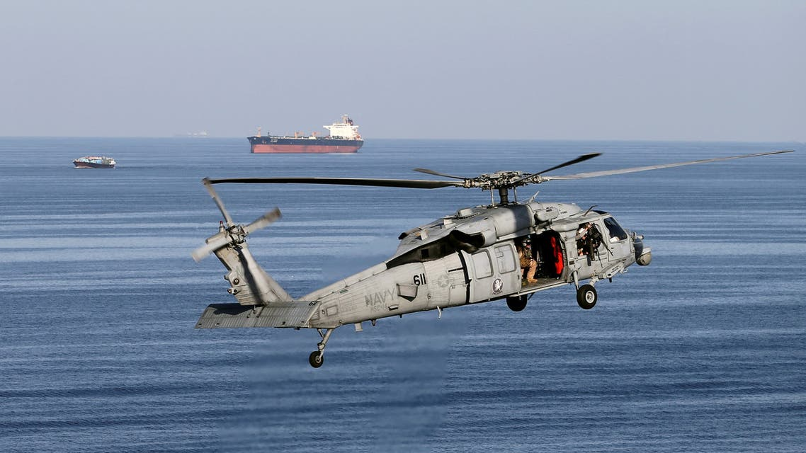 FILE PHOTO: A MH-60S helicopter hovers in the air with an oil tanker in the background as the USS John C. Stennis makes its way to the Gulf through the Strait of Hormuz, December 21, 2018. REUTERS/Hamad I Mohammed/File Photo