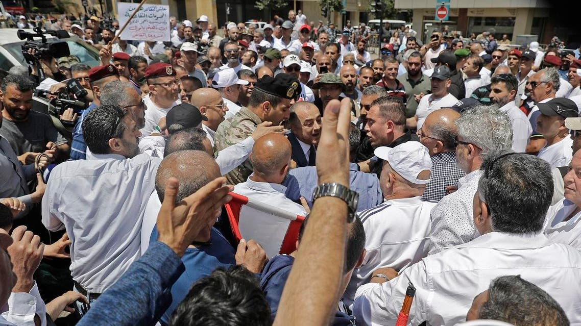 Lebanese army veterans react to the arrival of Minister of Defense Elias Bou Saab to talk to them as they demonstrate near the governmental palace in Beirut on May 10, 2019. (AFP)
