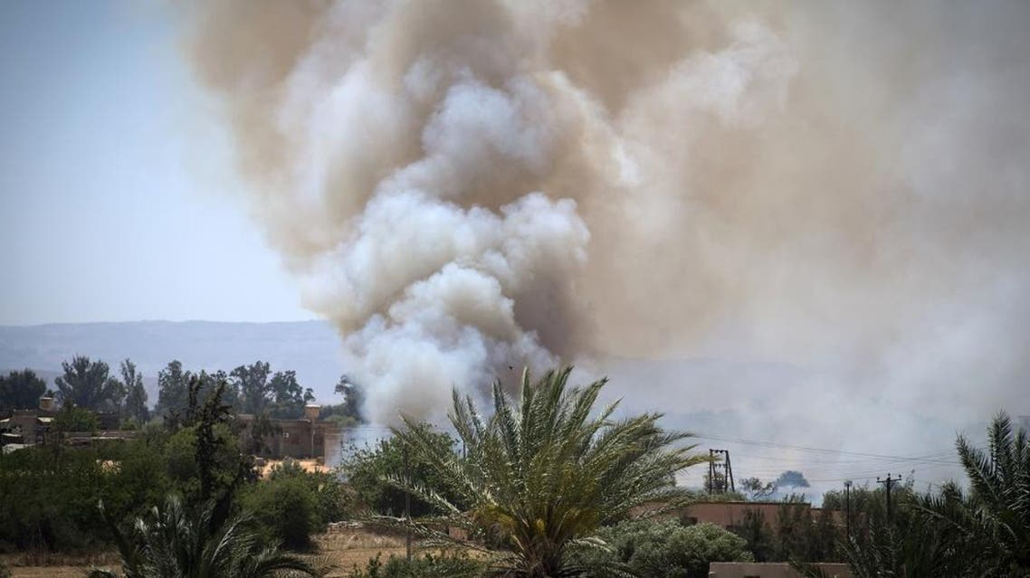 Heavy smoke rises above buildings during clashes about 40 kilometers south of the Tripoli on April 29, 2019. (AFP)